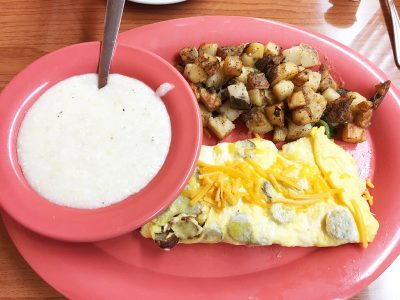 Sausage & Cheddar Omelet served with home fries and grits